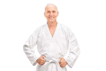 martial artist: Joyful senior in a white kimono with a white belt looking at the camera and smiling isolated on white background