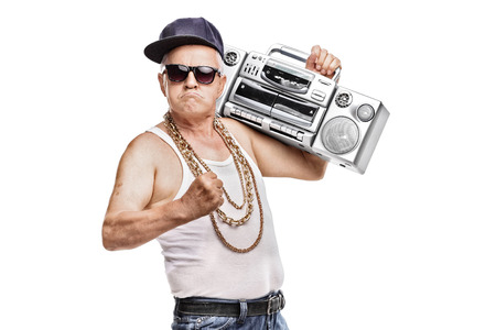 Mature man in hip-hop outfit holding a ghetto blaster and looking at the camera isolated on white background