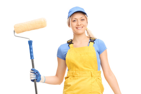 studio happy overall: Young female house painter in a yellow overall holding a paint roller isolated on white background