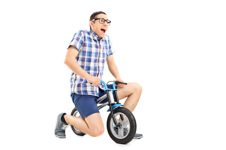 tiny: Studio shot of a silly young guy riding a tiny bicycle isolated on white background
