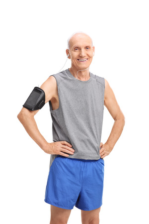 escucha activa: El estudio tiró de un hombre mayor en ropa deportiva, escuchar música en su teléfono celular y mirar a la cámara aislada en el fondo blanco Foto de archivo