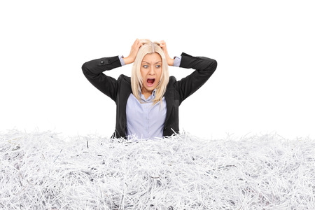 stuck: Studio shot of a young furious businesswoman stuck in a pile of shredded paper isolated on white background