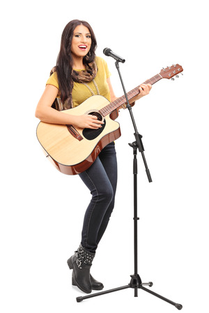 signer: Full length portrait of a female signer playing on acoustic guitar and singing on a microphone isolated on white background