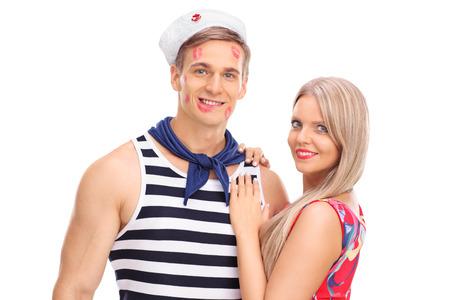 besos apasionados: Joven mujer posando con su novio marinero cubierto de marcas de l�piz labial beso aisladas sobre fondo blanco