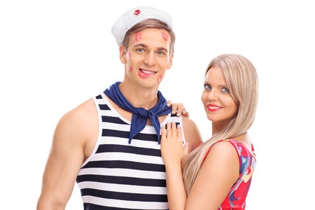 lipstick kiss: Young woman posing with her sailor boyfriend covered in lipstick kiss marks isolated on white background