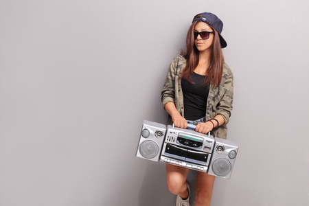 teenage girl: Cool teenage girl in hip hop outfit holding a ghetto blaster and leaning against a gray wall