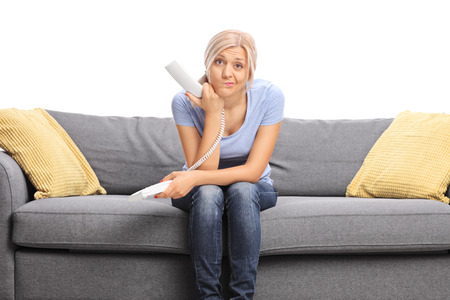 telephone: Displeased young woman sitting on a gray sofa and holding a telephone speaker isolated on white background