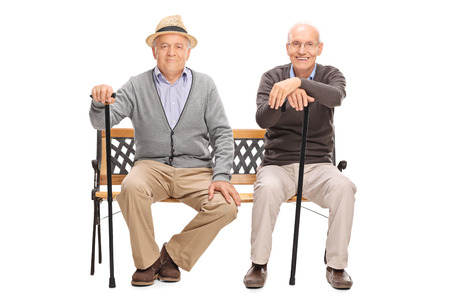 sit studio: Two senior gentlemen with black canes sitting on a wooden bench and looking at the camera isolated on white background Stock Photo