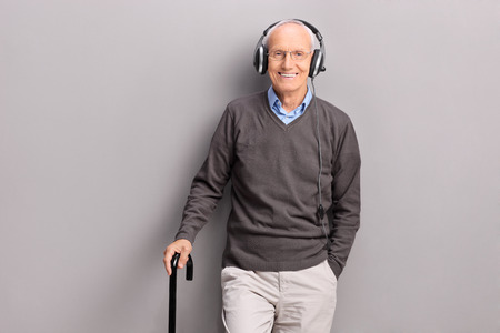 Senior gentleman with a cane listening music on headphones and posing against a gray wall Imagens