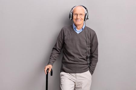 canne: Signore anziano con un bastone ascolto musica in cuffia e in posa contro un muro grigio Archivio Fotografico