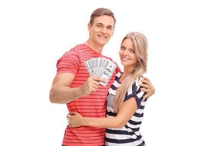 cash money: Hombre joven alegre celebración montón de dinero y posando con su novia aisladas sobre fondo blanco