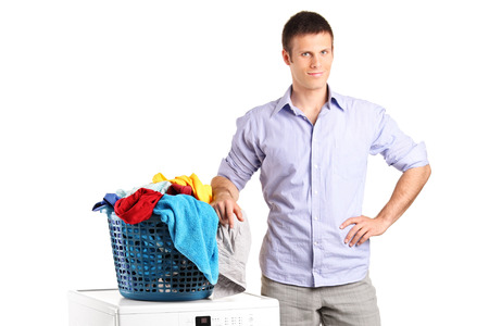it is isolated: Guy standing by a washing machine with a laundry basket on it isolated on white background Stock Photo