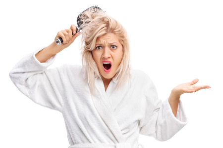 displeased: Displeased young woman in a white bathrobe with her hair tangled in a hairbrush isolated on white background