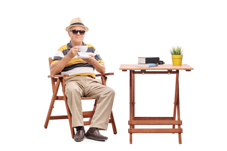 seated: Senior gentleman sitting at a coffee table and drinking a cup of coffee isolated on white background Stock Photo