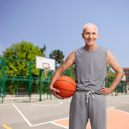 Vertical studio shot of a senior man in sportswear holding a basketball and looking at the camera at an outdoor baskeball court
