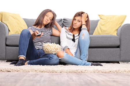 teenagers: Two bored teenage girls watching TV and changing the channels isolated on white background Stock Photo