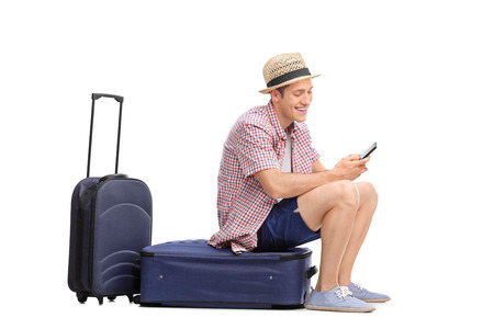 Young male tourist typing a text message on his cell phone an sitting on his luggage isolated on white background Reklamní fotografie