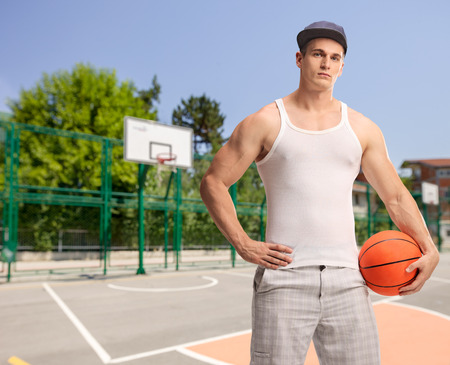 outdoor basketball court: Vertical shot of a young man with a blue cap holding a basketball and looking at the camera at an outdoor basketball court