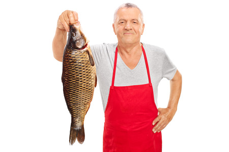 fishmonger: Mature fishmonger in a red apron holding a large freshwater fish and looking at the camera isolated on white background