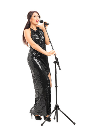 Full length portrait of a female singer in an elegant black dress singing on a microphone isolated on white background