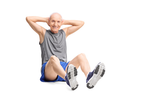 Active senior man in sportswear doing stomach crunches and looking at the camera isolated on white background Stock Photo