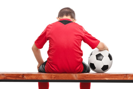 Niño pequeño triste en camiseta de fútbol roja sentado en un banco y sosteniendo una pelota aislados sobre fondo blanco Foto de archivo