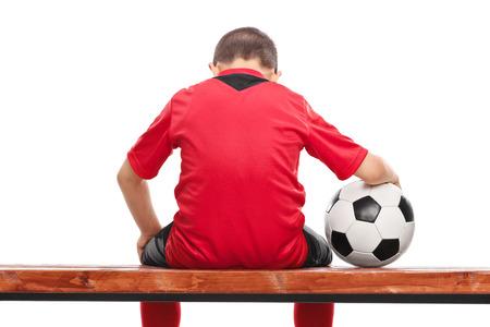 niños pensando: Niño pequeño triste en camiseta de fútbol roja sentado en un banco y sosteniendo una pelota aislados sobre fondo blanco Foto de archivo
