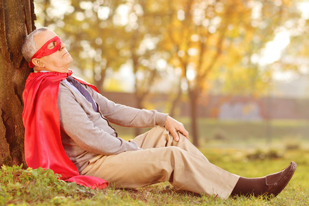 superhero cape: Senior in superhero outfit leaning on tree in park Stock Photo