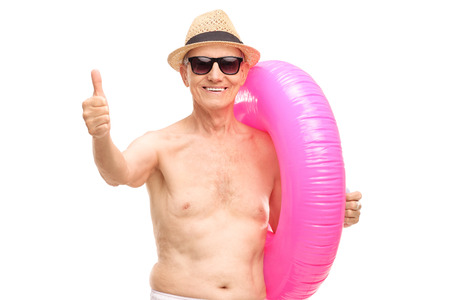 posing  agree: Senior man carrying a big pink swimming ring and giving a thumb up isolated on white
