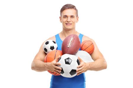 balones deportivos: Atleta joven sosteniendo un montón de diferentes tipos de balones deportivos aislados en el fondo blanco Foto de archivo