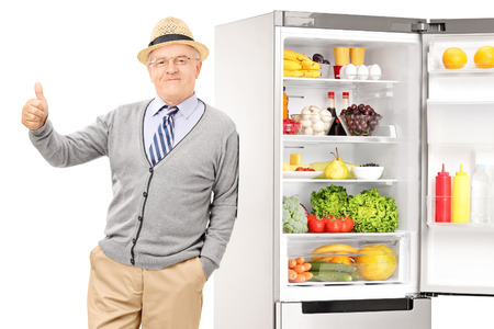 posing  agree: Senior leaning on a fridge and giving thumb up isolated on white