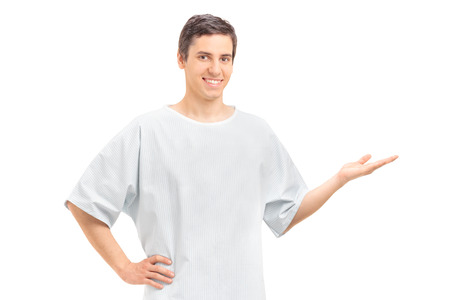 looking to camera: Young male patient in a hospital gown gesturing with his hand and looking at the camera isolated on white background Stock Photo