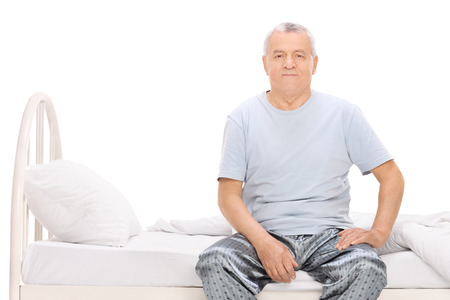 early 60s: Senior man in pajamas sitting on a bed isolated on white Stock Photo