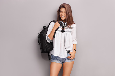 Teenage schoolgirl with headphones carrying a backpack and posing in front of a gray wall Stock Photo