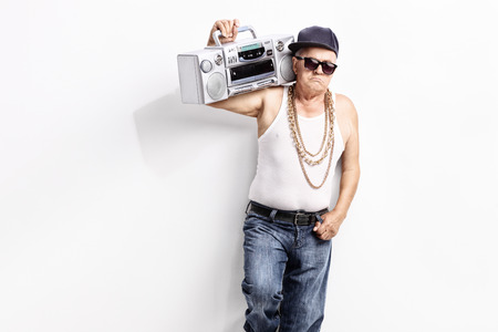 shoulder carrying: Senior man in a hip-hop outfit carrying ghetto blaster over his shoulder and looking at the camera Stock Photo