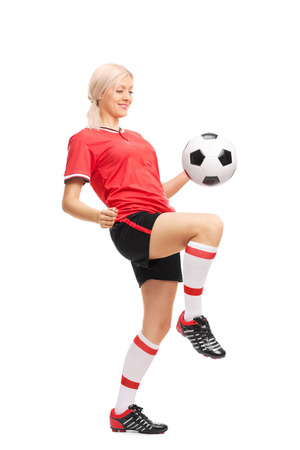 Volledige lengte portret van een jonge vrouwelijke voetballer in een rode trui en zwarte broek jongleren een voetbal op een witte achtergrond