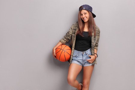 Cool teenage girl holding a basketball and leaning against a gray wall