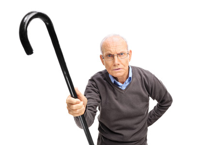 displeased: Displeased senior holding a black cane and scolding someone towards the camera isolated on white background Stock Photo