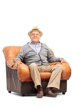 seated man: Estudio tiro vertical de un caballero alto relajado sentado en un cómodo sillón y mirando a la cámara aislada en el fondo blanco