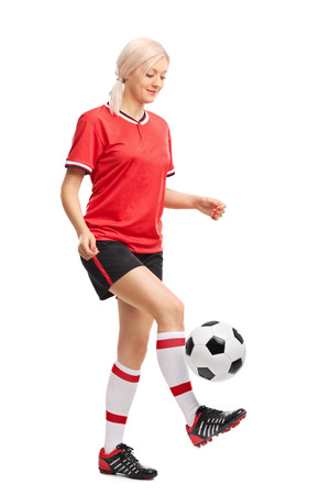 girl kick: Full length portrait of a female soccer player juggling a ball and smiling isolated on white background Stock Photo
