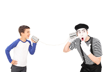 comedian: Studio shot of a little kid talking to a young male comedian through a tin can phone isolated on white background