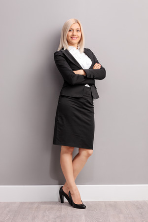 office wear: Full length portrait of a young businesswoman in black suit leaning against a gray wall and looking at the camera