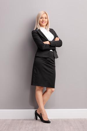 Full length Portret van een jonge zakenvrouw in zwart pak leunend tegen een grijze muur en kijken naar de camera Stockfoto