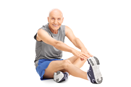 old: Studio shot of a senior in sportswear stretching his leg seated on the floor isolated on white background Stock Photo