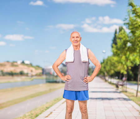 happy senior: Active senior man in sportswear with a towel around his neck standing on a sidewalk and looking at the camera shot with tilt and shift lens