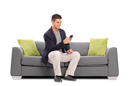 쾌활 한 젊은 남자 회색 소파에 앉아 및 흰색 배경에 고립 된 자신의 휴대 전화에 입력