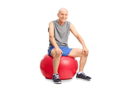 hombre sentado: Hombre mayor alegre en ropa deportiva sentado en una bola roja de la aptitud y mirando a la cámara aislada en el fondo blanco