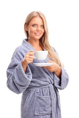 mujer sola: Vertical shot of a beautiful blond woman holding a cup of coffee and looking at the camera isolated on white background