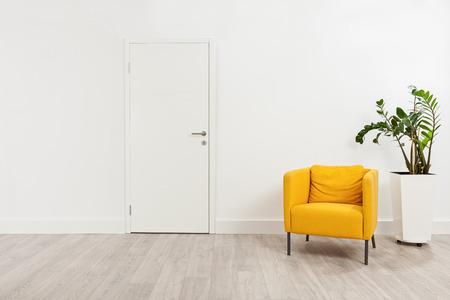 cerrar puerta: Sala de espera moderna con un sillón de color amarillo y una planta en una maceta blanco detrás de él Foto de archivo