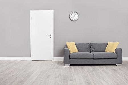 벽에 문 앞의 현대적인 회색 소파와 시계와 빈 대기실 스톡 콘텐츠